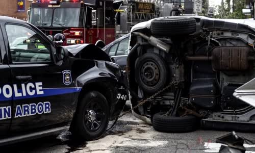 Cop runs red light and causes rollover crash