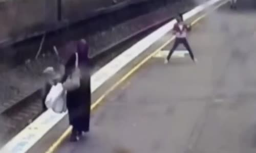 Woman saves schoolgirl from train tracks